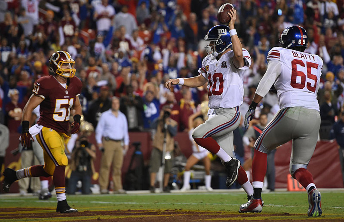 Eli Manning threw four touchdown passes and ran in another as the Giants blew out the Redskins 45-14 on Thursday night. (Patrick Smith/Getty Images)