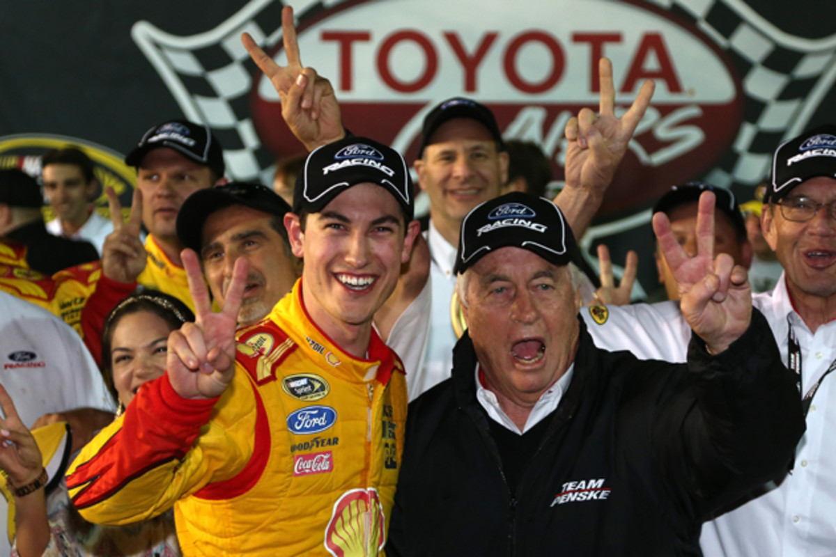 Joey Logano, driver of the #22 Shell-Pennzoil Ford, celebrates in Victory Lane with team owner Roger Penske after winning the NASCAR Sprint Cup Series.