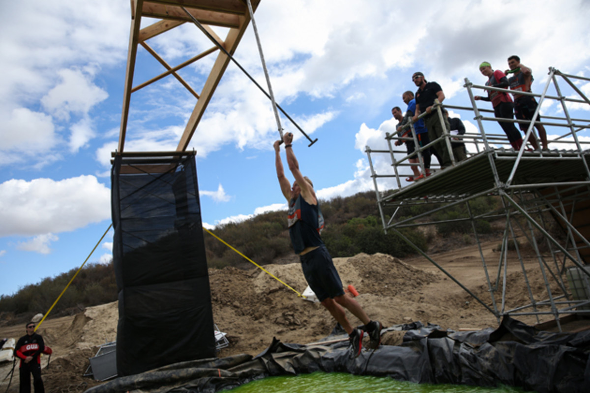 Murphy hangs on during Tough Mudder test obstacle, Swingers.
