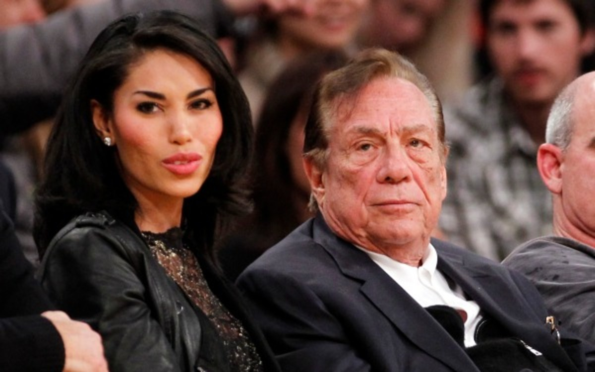 Dec. 19, 2010, file photo, Los Angeles Clippers owner Donald Sterling, third right, sits with V. Stiviano, left, as they watch the Clippers play the Los Angeles Lakers during an NBA preseason basketball game in Los Angeles. NBA commissioner Adam Silver announced Tuesday, April 29, 2014, that he is banning the owner for life from the Clippers organization over racist comments in recording. (AP Photo/Danny Moloshok, File)