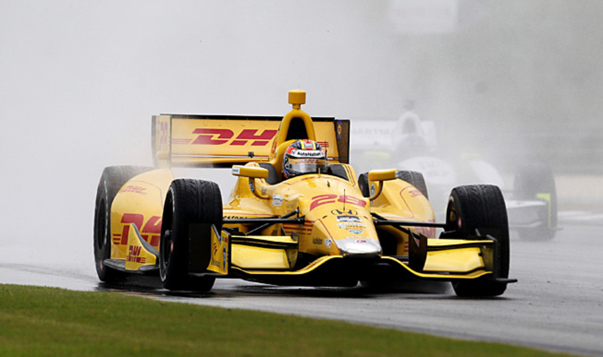 Ryan Hunter-Reay kicks up water spray as he leads the pack down the Alabama Grand Prix backstretch.