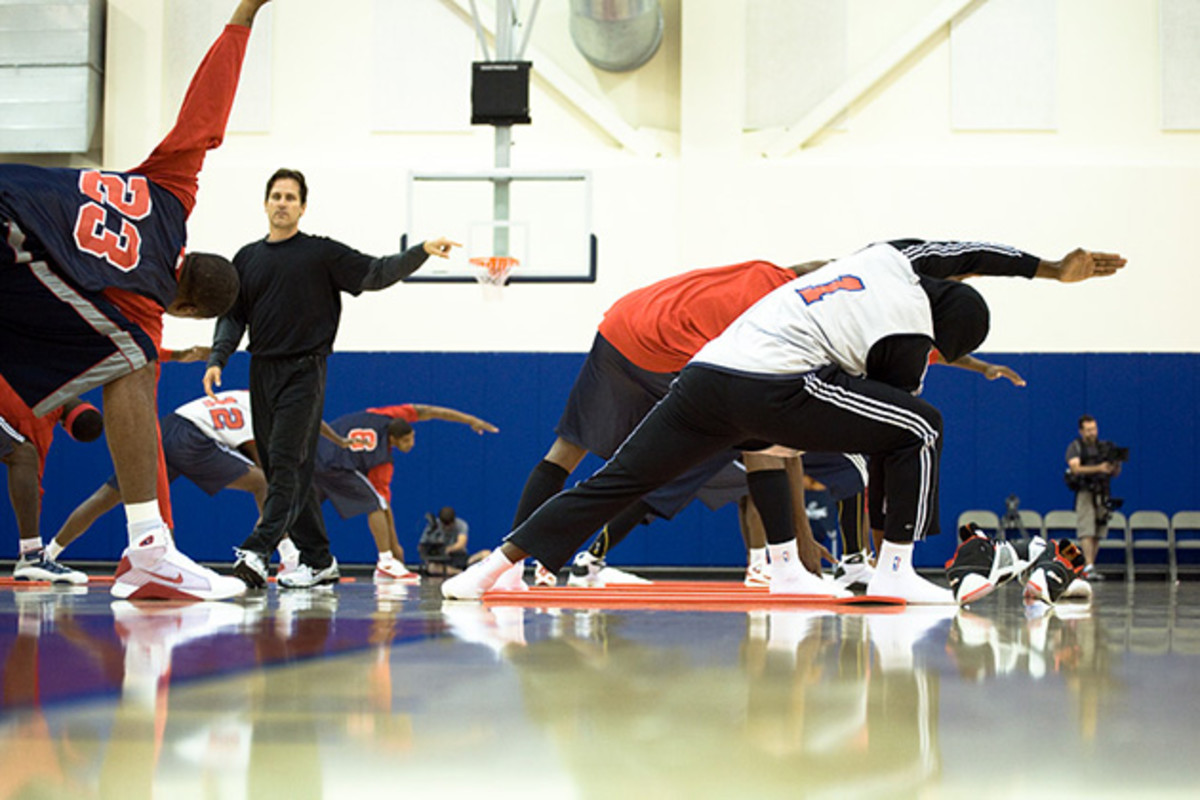 Kent Katich leading a group yoga class of professional basketball players.