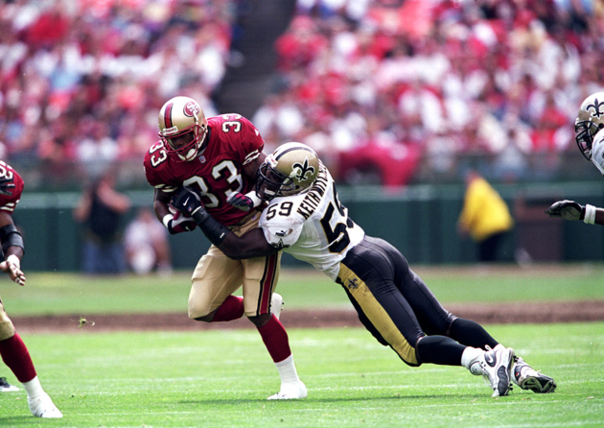 Lawrence Phillips (33) of the San Francisco 49ers moves with the ball as Keith Mitchell (59) of the New Orleans Saints tries to tackle him.