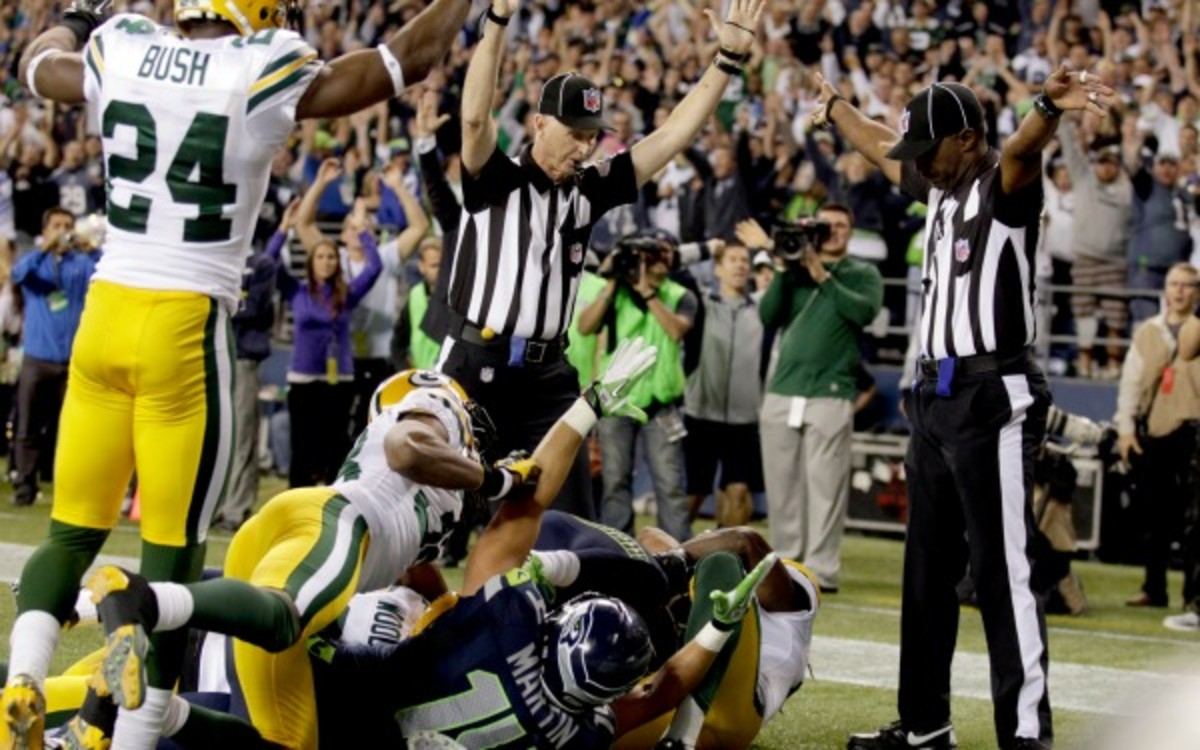 In this Sep.t 24, 2012, file photo, a replacement official signals a touchdown by Seattle Seahawks wide receiver Golden Tate, obscured, on the last play of an NFL football game against the Green Bay Packers in Seattle. The Seahawks won 14-12. (AP Photo/Stephen Brashear)