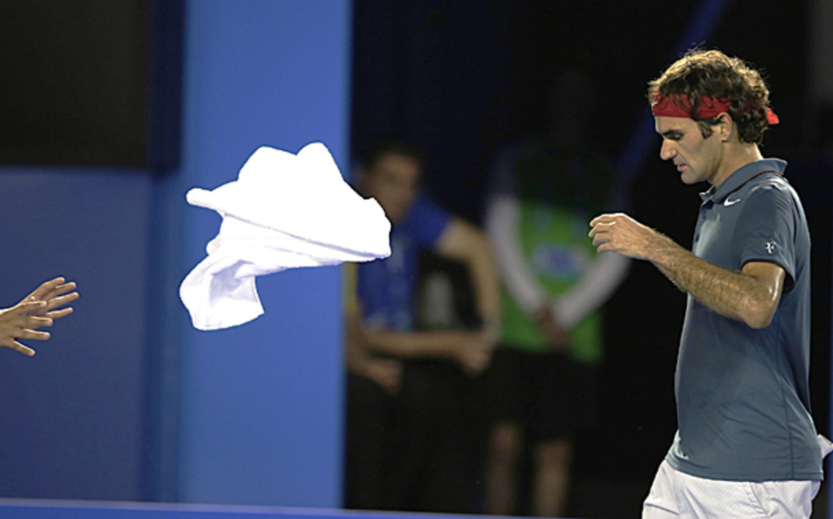 Roger Federer tosses his towel to the outstretched hands of a ball kid. (Rick Rycroft/AP)