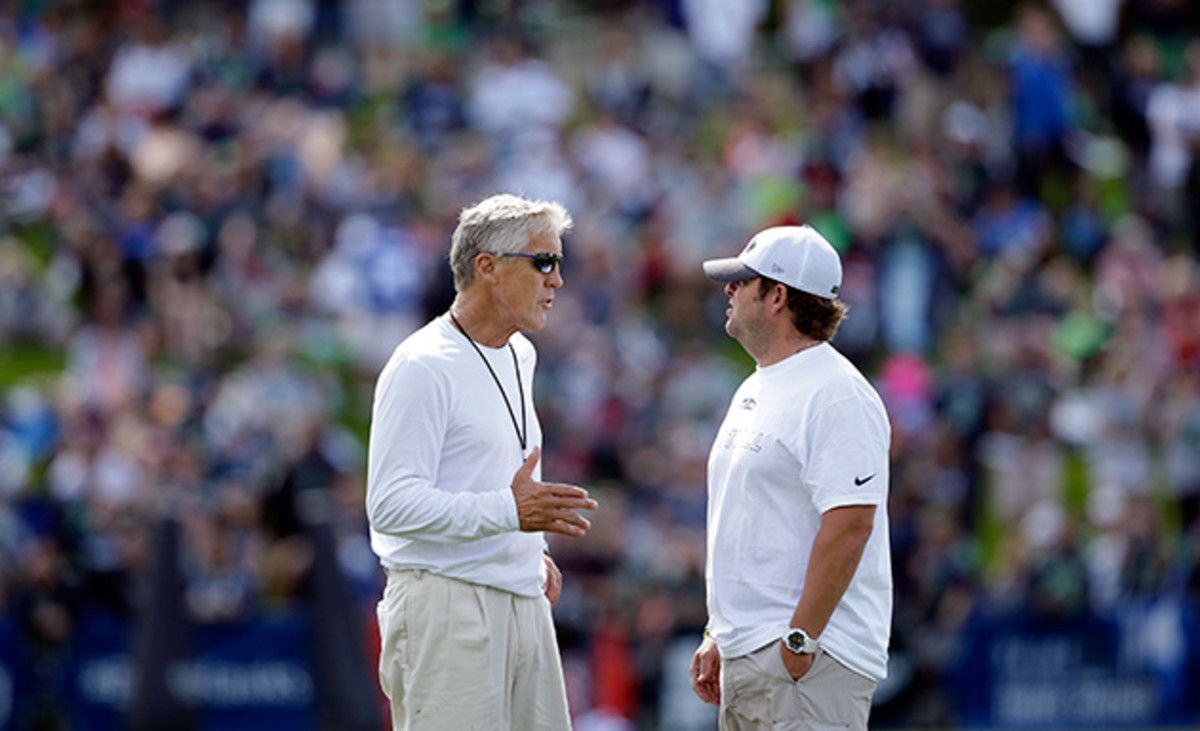 Seattle Seahawks head coach Pete Carroll, left, talks with general manager John Schneider as fans fill a hill behind at an NFL football camp practice Friday, July 25, 2014, in Renton, Wash.