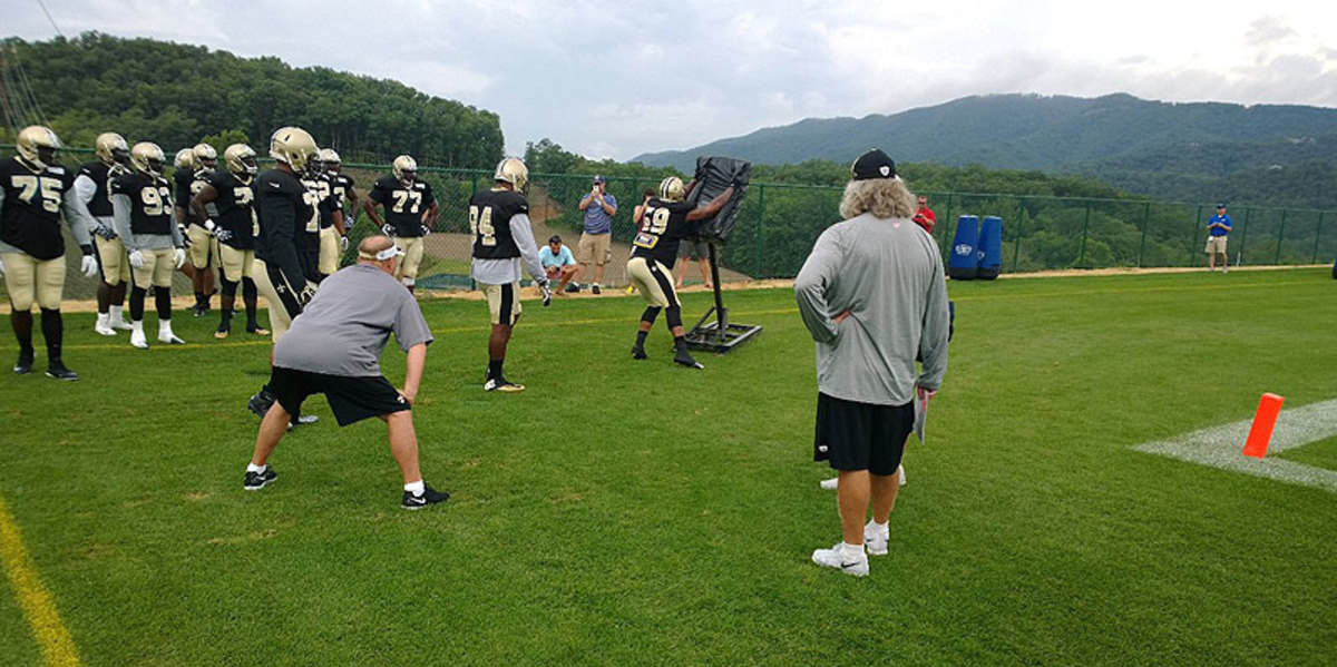 Defensive line coach Bill Johnson, left, and coordinator Rob Ryan watch linebacker Rufus Johnson Jr. stand the individual sled up. Pro Bowl defensive end Cam Jordan is on deck. (Photo by Peter King/The MMQB)