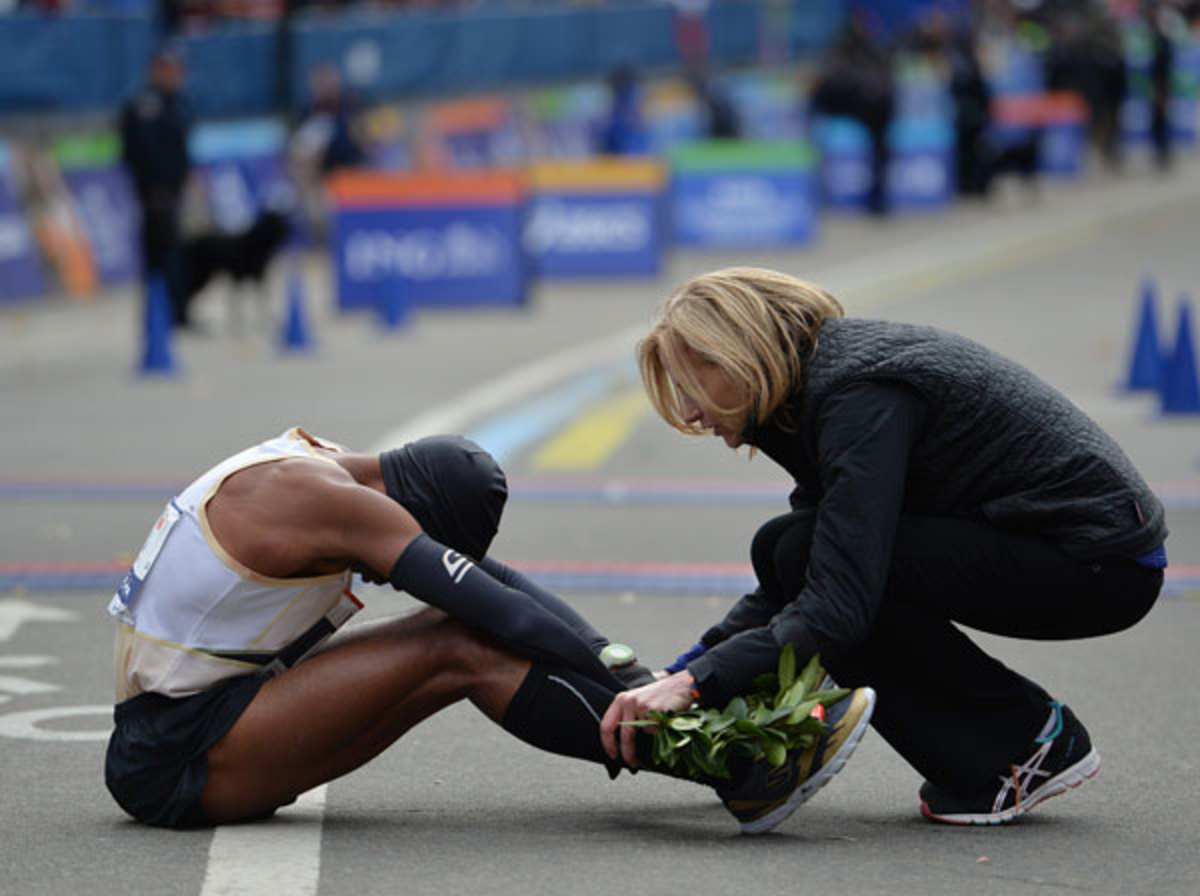 Meb Keflezighi is greeted by New York Road Runners President Mary Wittenberg after he crossing the finish line in the New York City Marathon in November 2013.