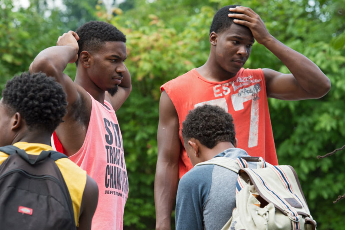 Raequan Stallings (left) and RANDALL CAESER wait for the bus to arrive at McCluer High to take them to practice.