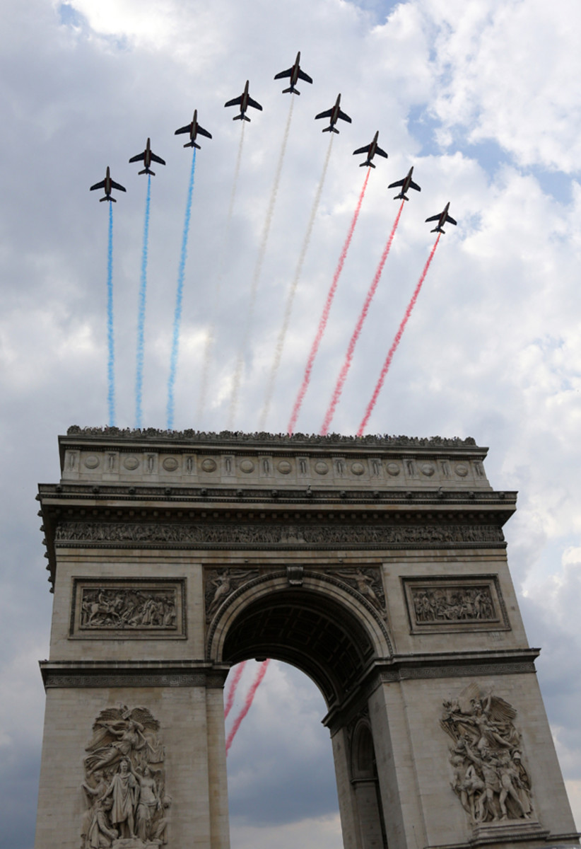 The French Air Force aerobatics squad, the Patrouille de France, flies over the Arc de Triomphe to celebrate the twenty one and last stage of the 2014 Tour de France.