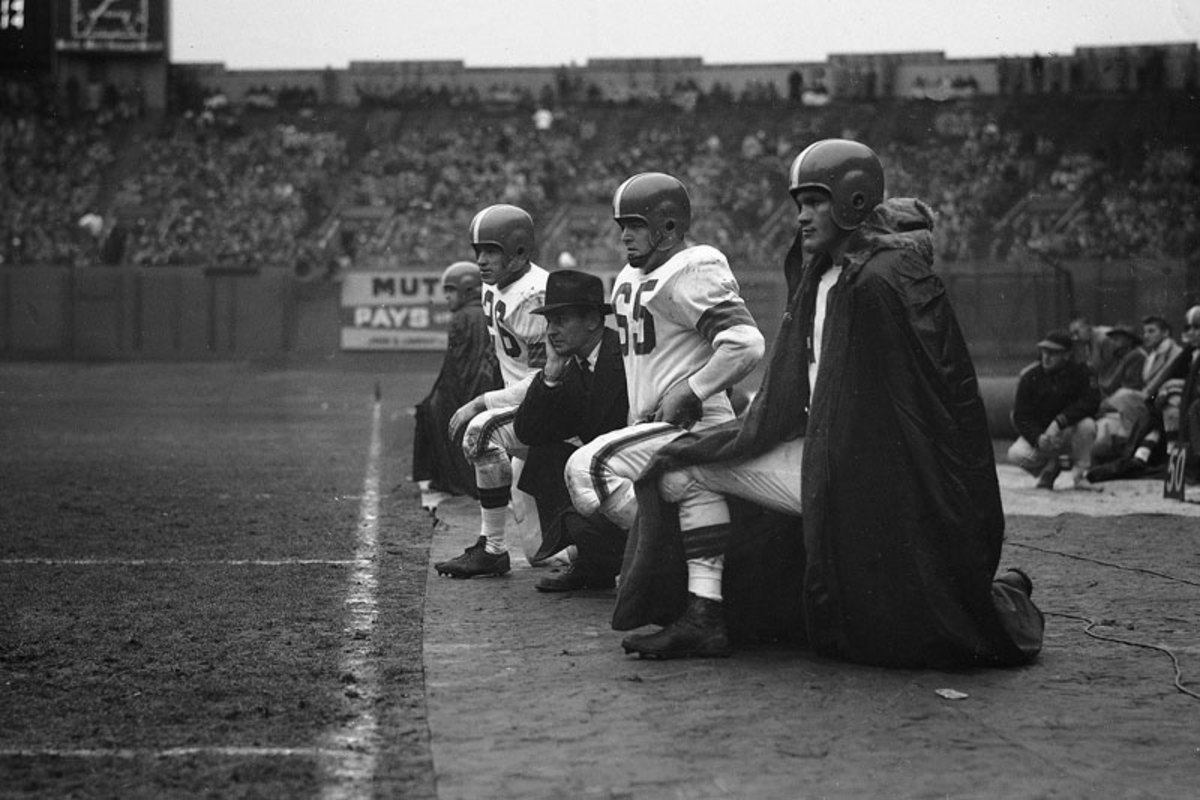 On Dec. 8, 1953, Cleveland Browns coach Paul Brown is flanked by (from l. to r.) halfback Ray Renfro, guard Chuck Noll (65) and halfback Billy Reynolds. (AP)