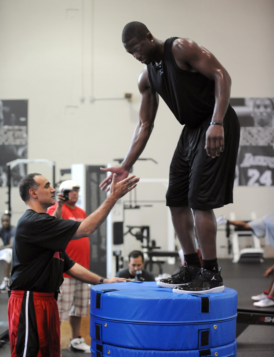 Dwyane Wade gets a hand from Tim Grover during one of his vertical leap workouts at ATTACK Athletics in Chicago, Illinois.