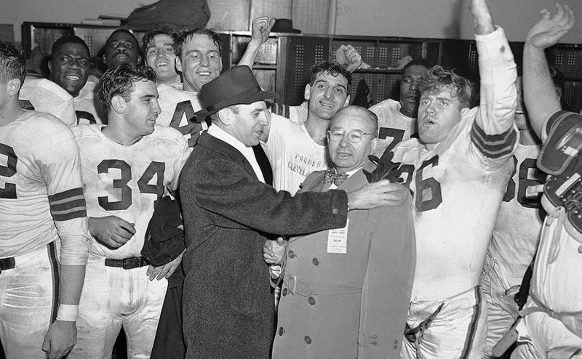 Paul Brown (left) and owner Mickey McBride celebrate with the team after the Browns won their second straight AAFC title in December 1947. (AP)