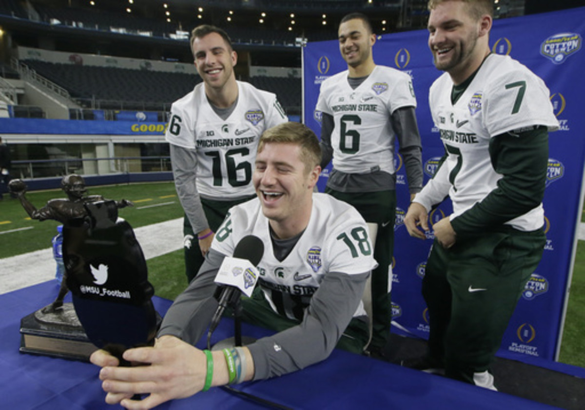 Michigan State quarterback Connor Cook (18) makes a photo of himself with fellow quarterbacks Tommy Vento (16), Damion Terry (6) and Tyler O'Connor (7) during the media day for the NCAA Cotton Bowl college football game Tuesday, Dec. 29, 2015, in Arlingto