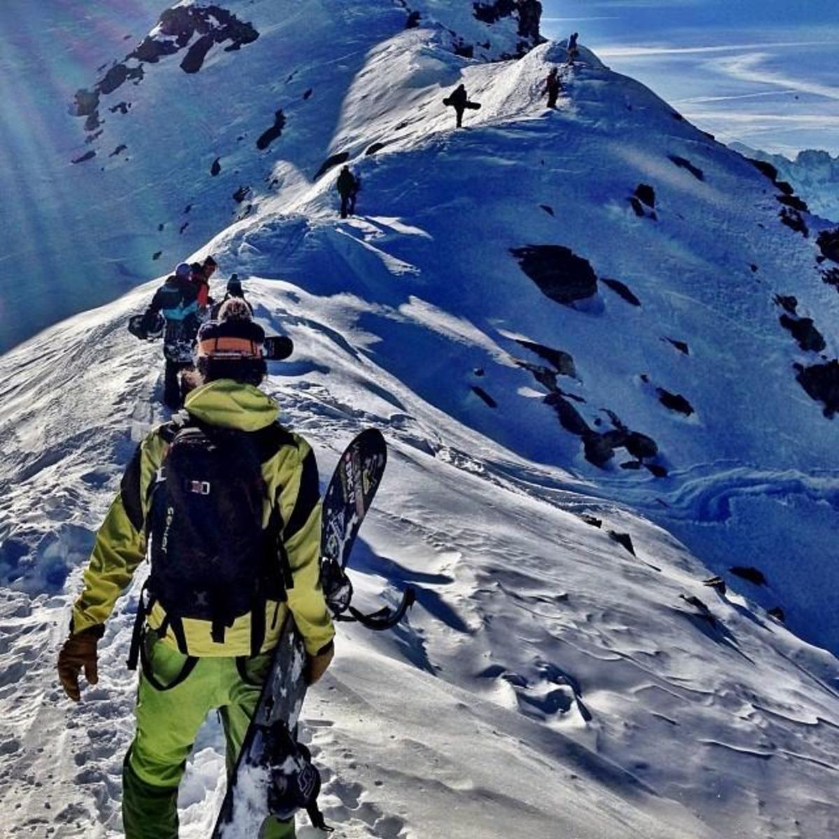 Snowboarder Jeremy Jones treks along the ridge of a mountain with his crew.