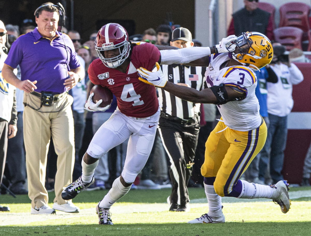 Jerry Jeudy tries to break a tackle in front of Ed Oregeron