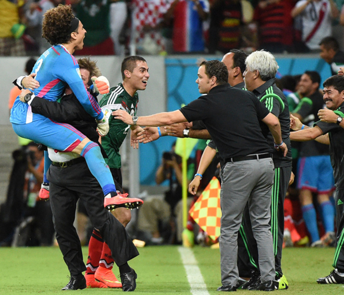 Miguel Herrera, second left, hoists goalkeeper Guillermo Ochoa in celebrating Mexico's 3-1 win over Croatia to seal El Tri's place in the round of 16.