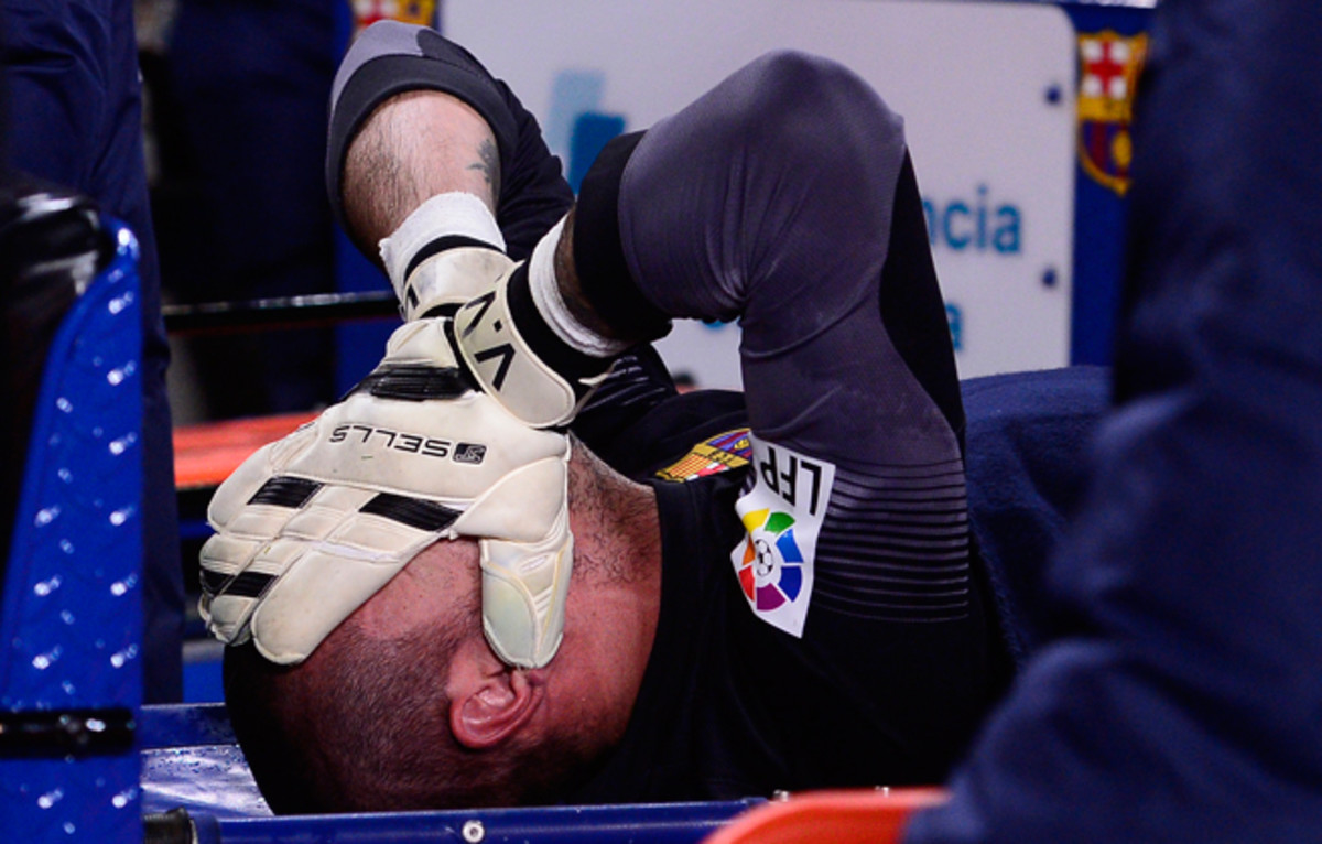 Victor Valdes reacts as he is carted off the field after suffering a suspected knee injury in Barcelona's match win over Celta Vigo on Wednesday.