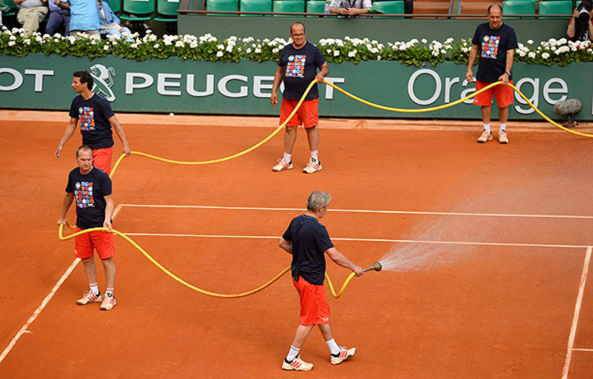 The Roland Garros grounds crew waters the court before the women's semifinals in 2013. (Bob Martin/SI)