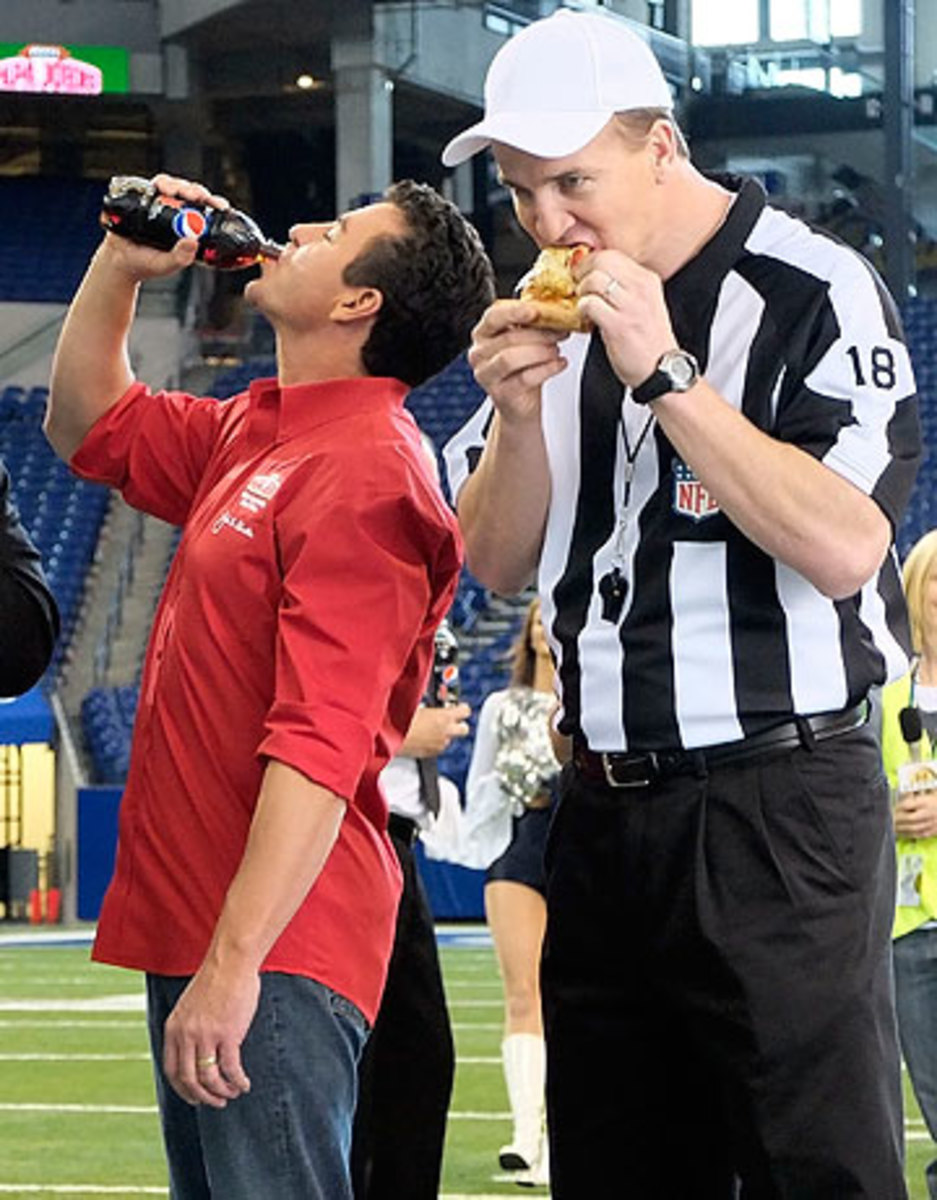 Manning, shown here filming a commercial for Papa John's, owns more than a dozen of the pizza company's franchises in Colorado. (AJ Mast/AP)