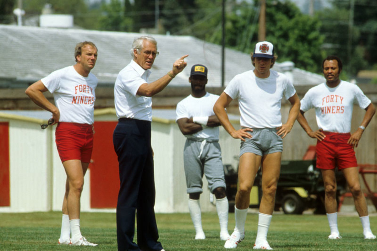 Walsh pictured with Montana (right) and Sam Wyche (far left), one of the many disciples who would go on to spread the gospel in the ensuing decades. (Carl Iwasaki/Sports Illustrated)