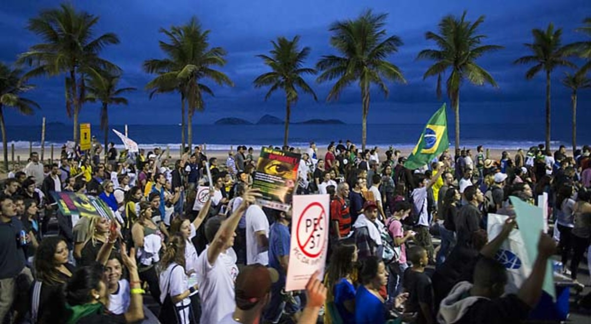 People march toward the home of Sergio Cabral, the governor of Rio de Janeiro state, to stage a protest Sunday.