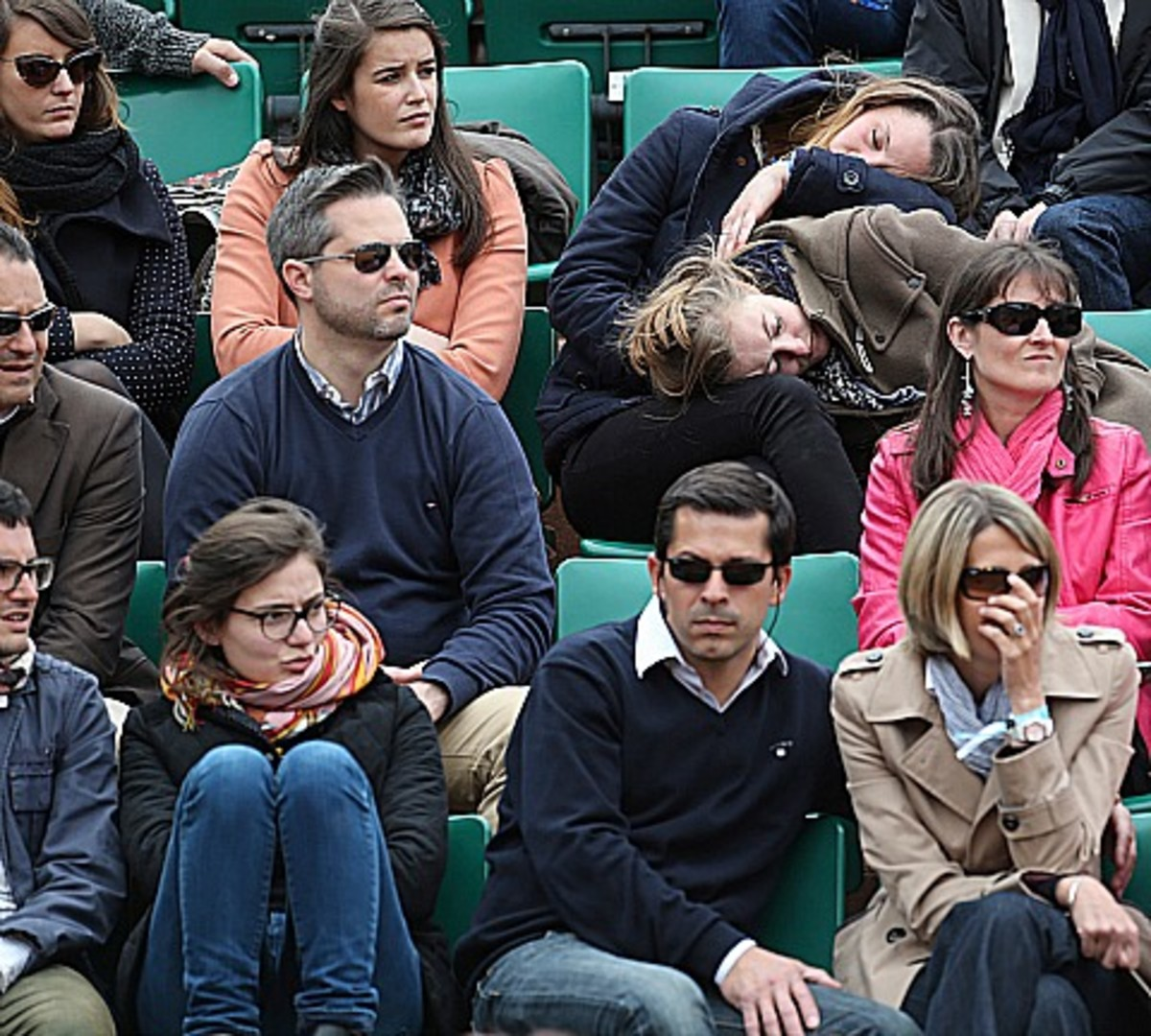 Two women sleep while Spain's David Ferrer plays against Australia's Marinko Matosevic in their first round match of the French Open tennis tournament, at Roland Garros stadium in Paris, Sunday, May 26, 2013. (AP Photo/Michel Euler)