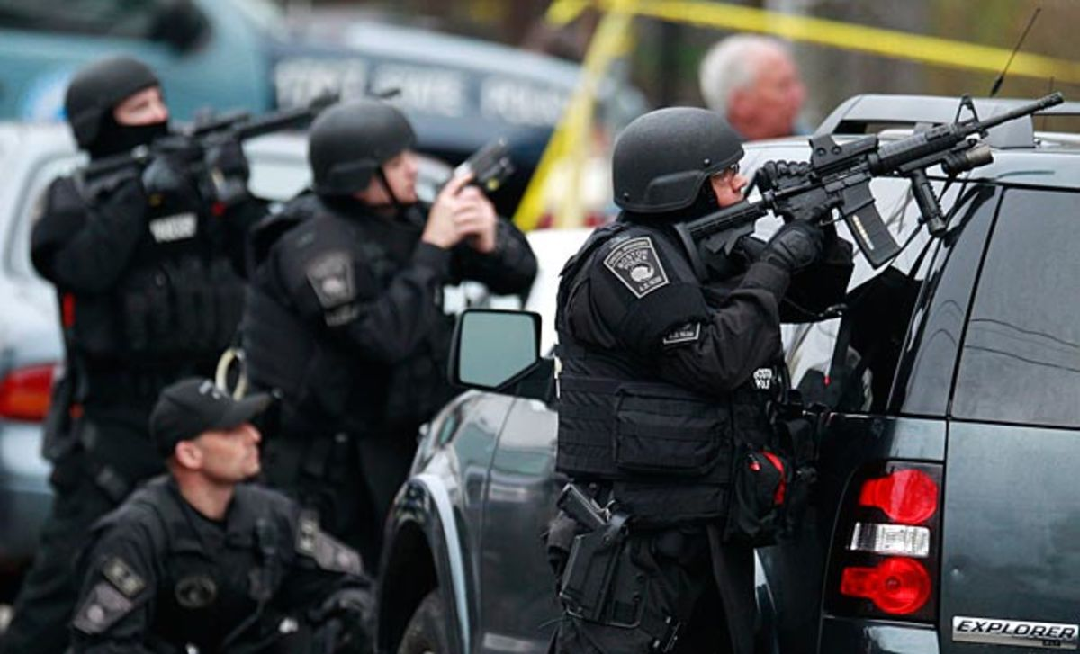 Police surround an apartment building while looking for a bombing suspect in Watertown, Mass.