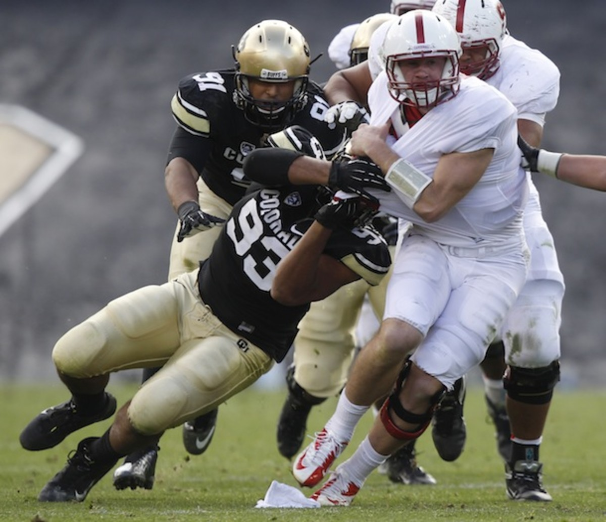 At left, Samson Kafovalu tackles Stanford's Kevin Hogan as though he were a short brick wall. (AP)