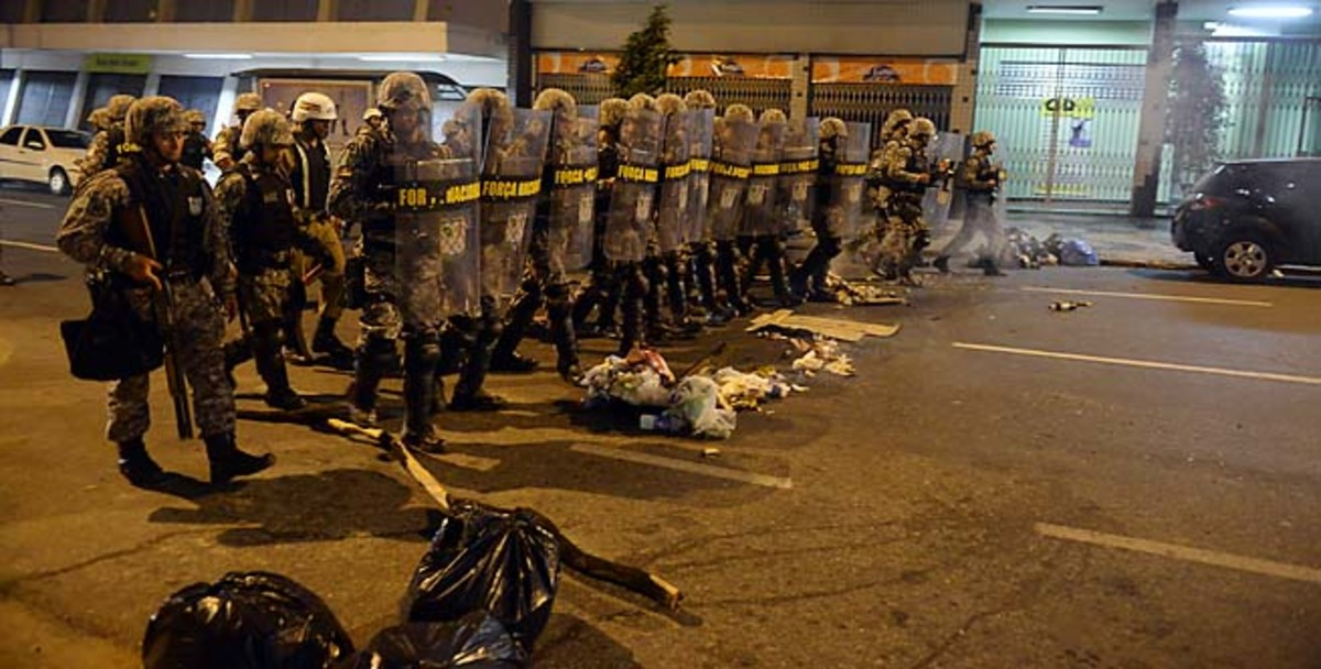 Policemen move into position in the street during Saturday's protests in Belo Horizonte.
