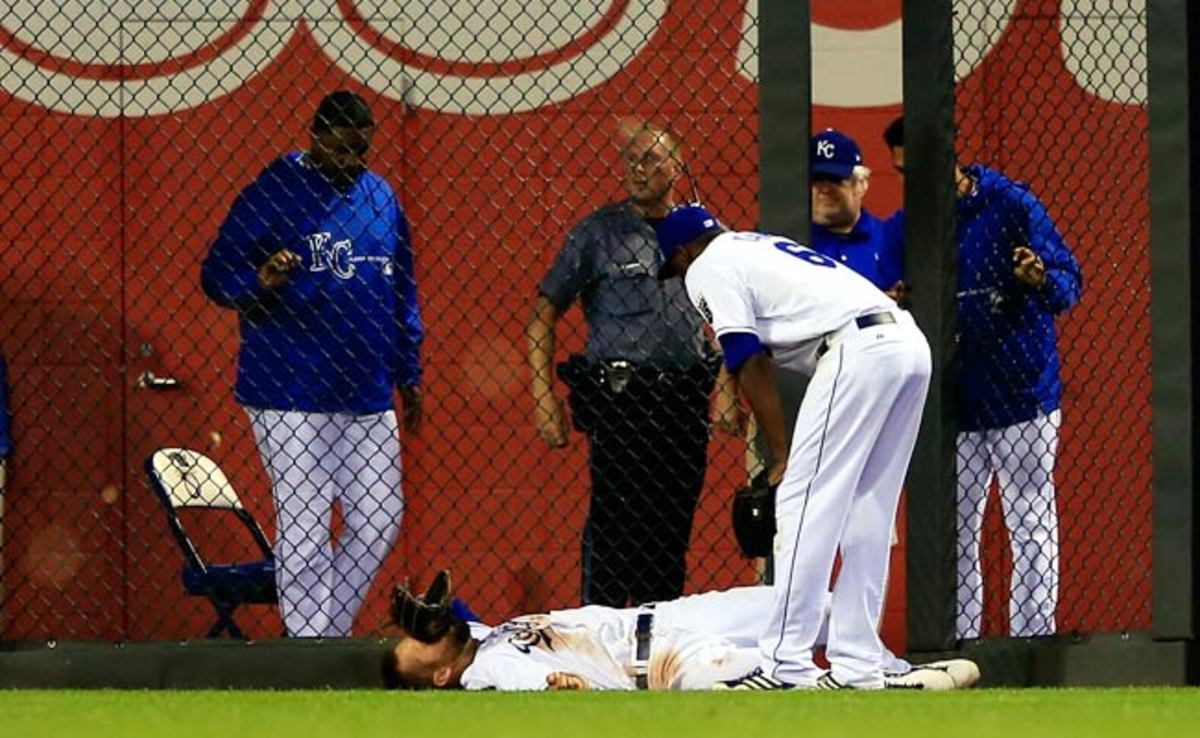 Lorenzo Cain stands over teammate Alex Gordon after Gordon hit his head against the outfield fence.