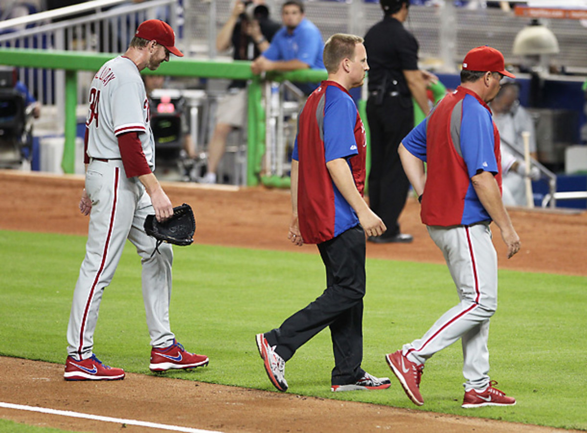 Roy Halladay left his start on Monday in obvious fatigue, sweating profusely and favoring his right arm. (Marc Serota/Getty Images)