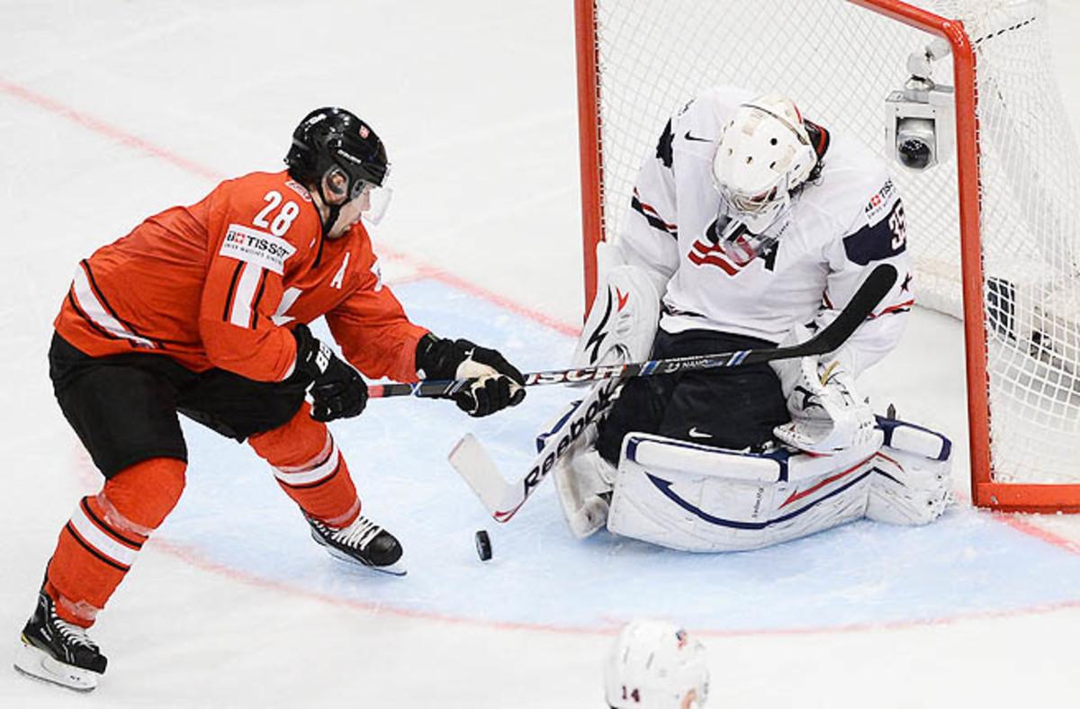 Switzerland's Martin Pluss (L) in action against US goalie John Gibson during the Ice Hockey IIHF World Championships.