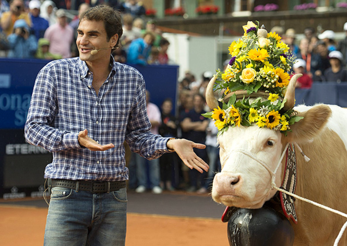 Roger Federer appears completely thrilled with his gift of a cow, since that's a perfectly normal way to thank someone. (PETER SCHNEIDER/EPA)