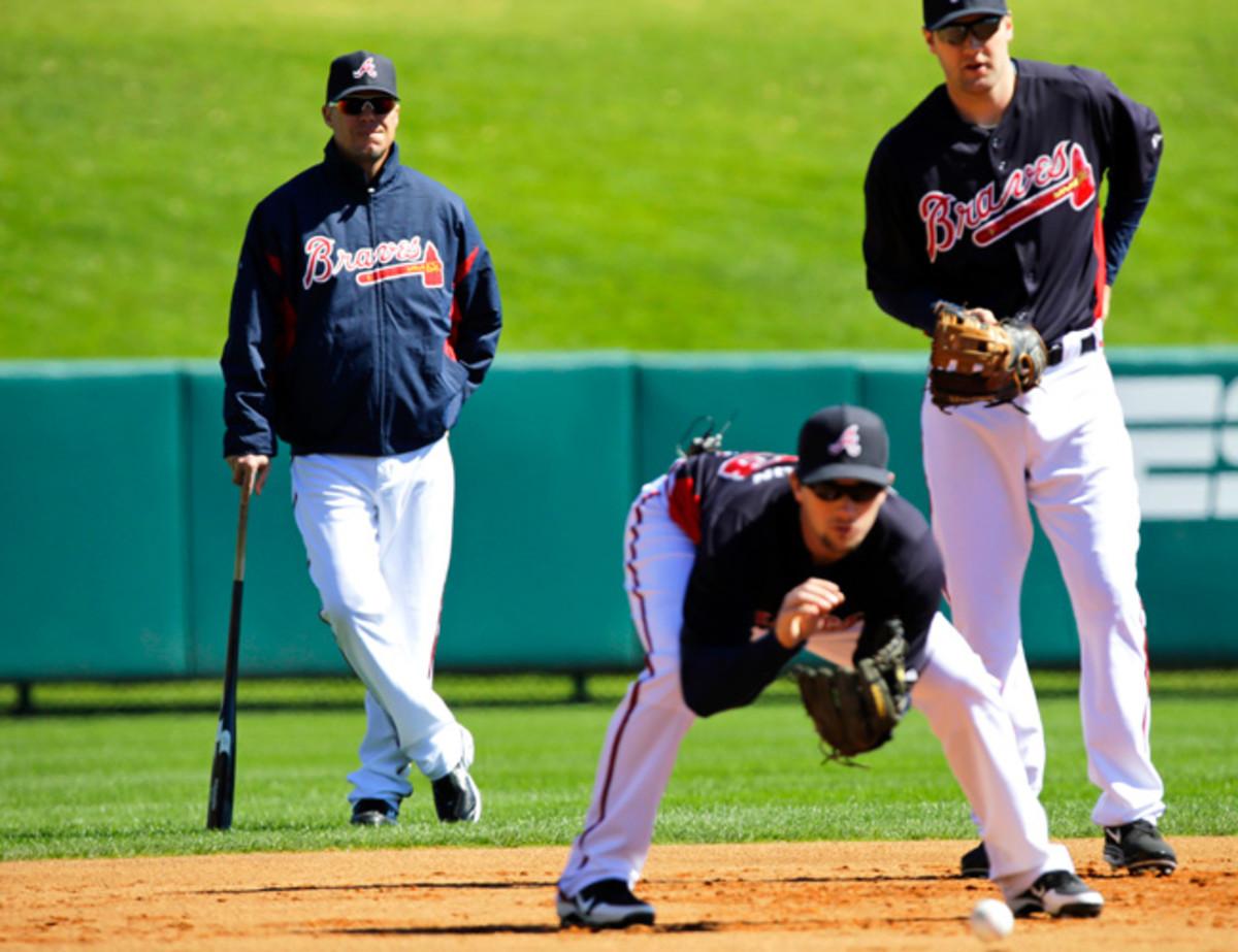 Former Braves third baseman Chipper Jones looks on as current third baseman Chris Johnson fields a ground ball