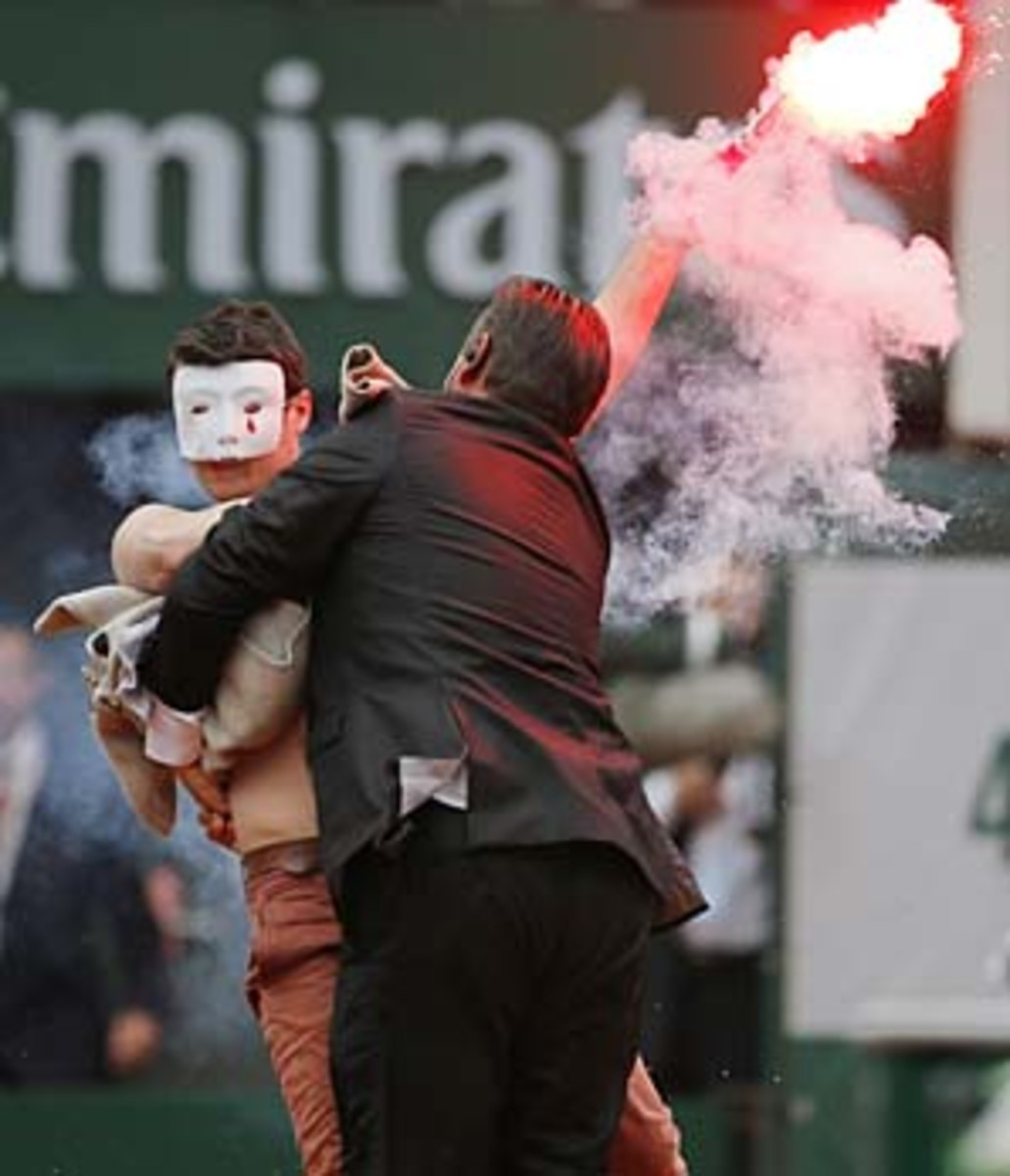 A security guard grabs a demonstrator who ran on court. (Michel Spingler/AP)