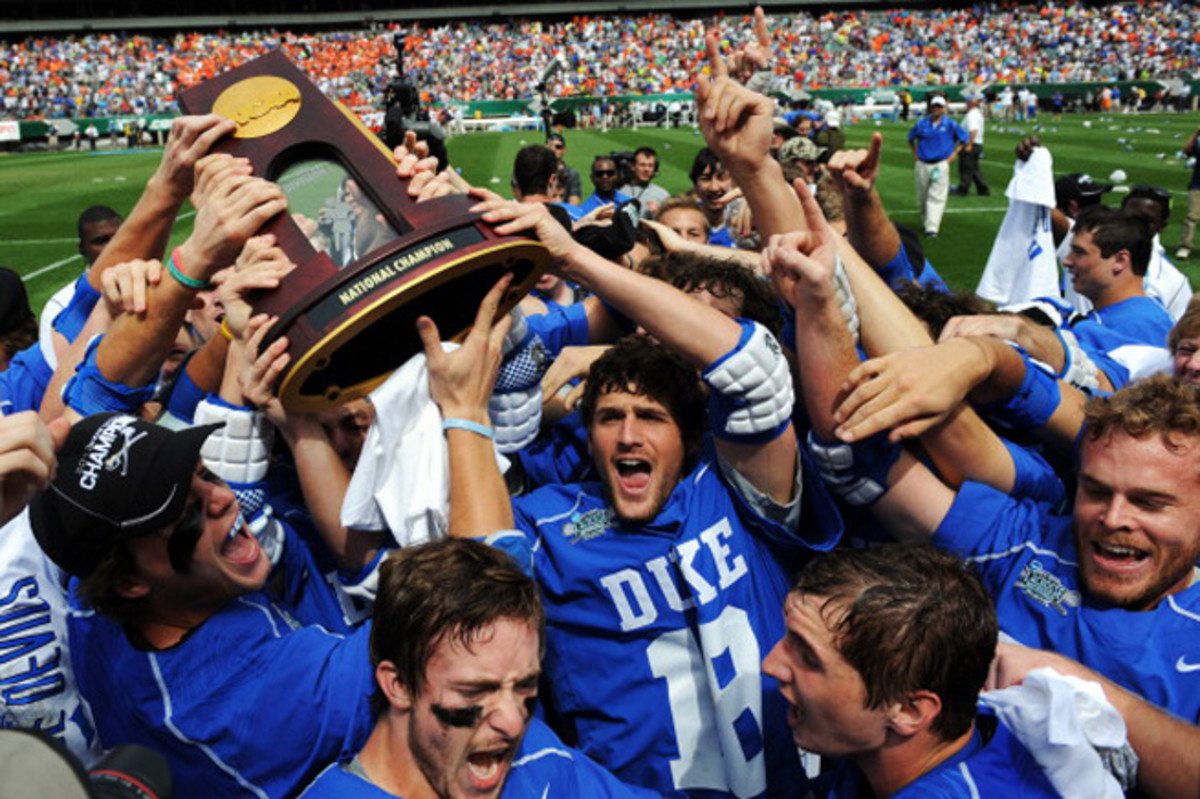 Duke's Tommy Patterson helps hoist the championship trophy after the Blue Devils topped Syracuse.