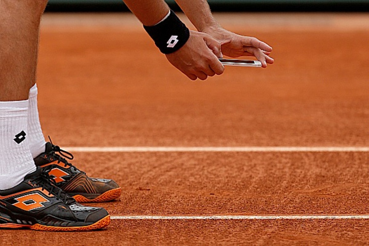 Sergey Stakhovsky takes a picture of a ball mark during his first round loss to Richard Gasquet. (AP Photo/Michel Spingler)