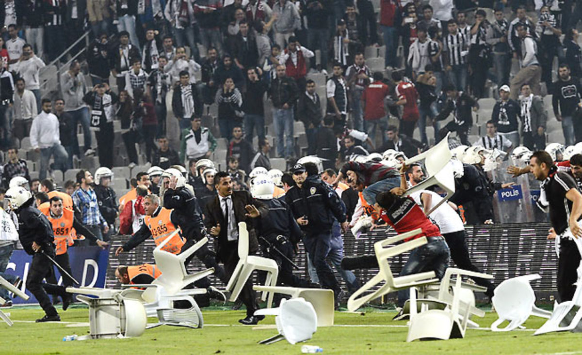 Fans invaded the pitch at Besiktas' match with rival Galatasary in Istanbul and threw chairs at police.