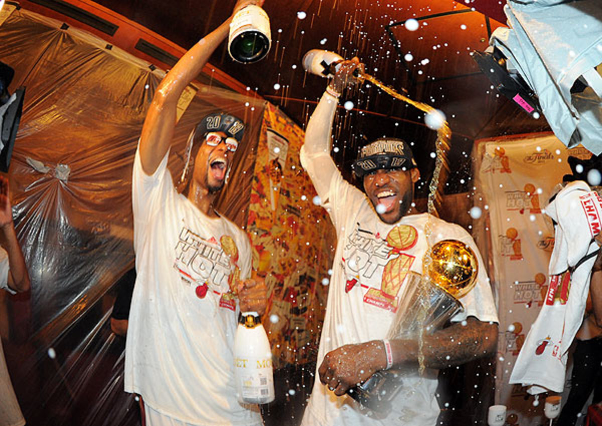 Miami Heat's LeBron James (right) and Chris Bosh brought out the champagne after winning the 2012-13 title.