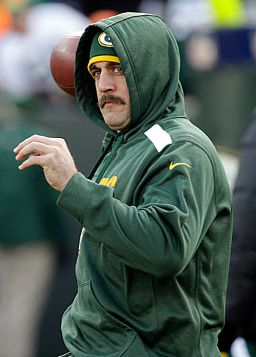 Not yet, Aaron—Rodgers tossed on the sideline on Sunday and no doubt would love to play on Thanksgiving even at less than 100 percent. (Mike Roemer/AP)