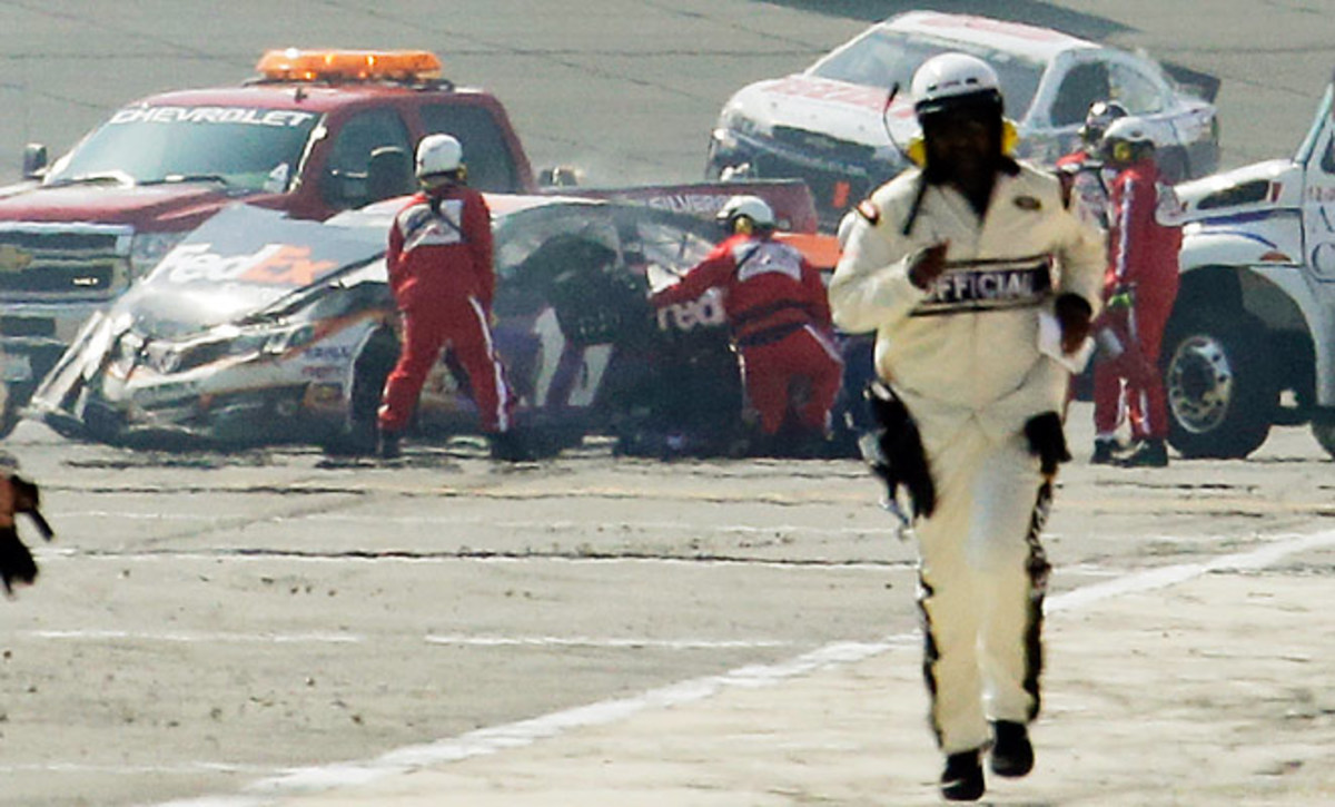 Rescue workers tend to the wreckage of Denny Hamlin's car after he collided with Joey Logano on the final lap of the NASCAR Sprint Cup series auto race in Fontana, Ca. .