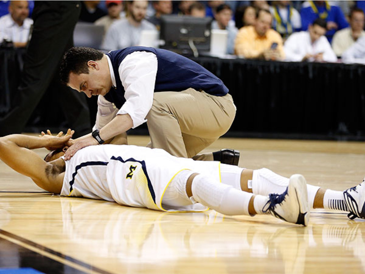 After getting tangled with Jackrabbits' Nate Wolters, Trey Burke hit the hardwood and was helped off by a trainer. (Gregory Shamus/Getty Images)
