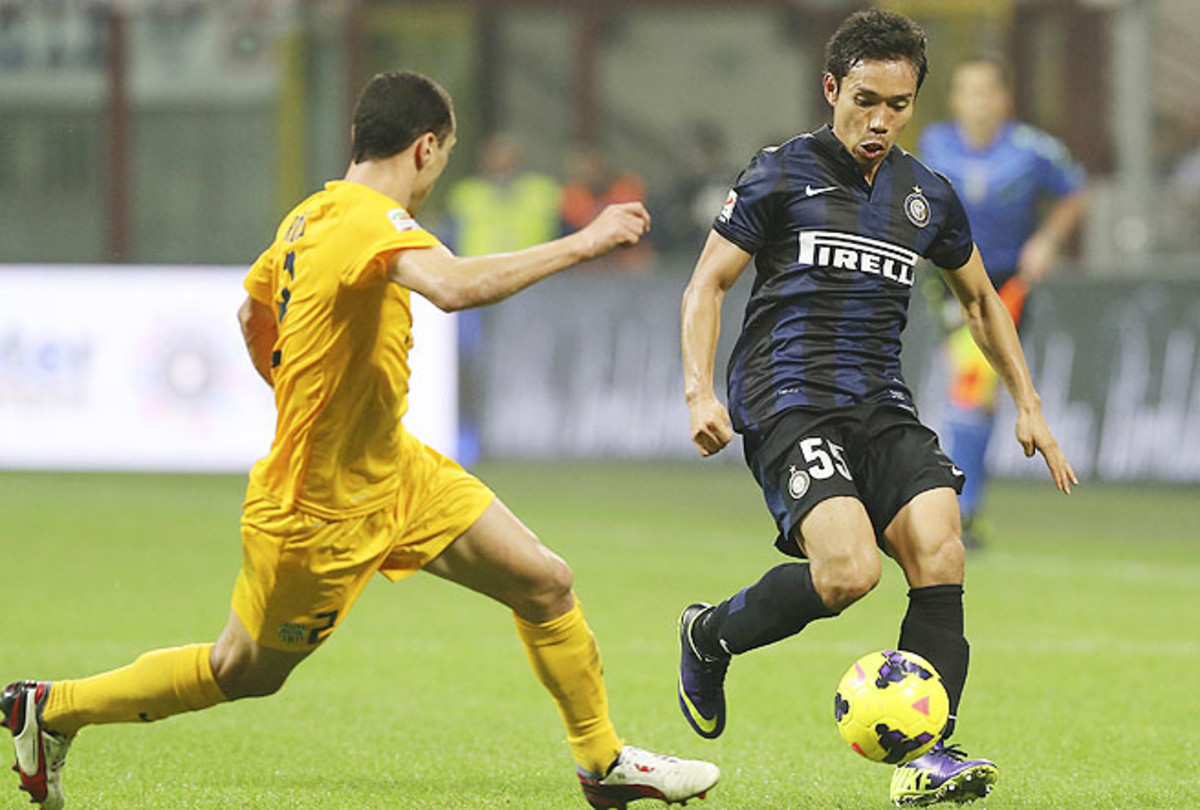 Inter Milan defender Yuto Nagatomo, right, challenges Hellas Verona Brazilian midfielder Romulo Souza.