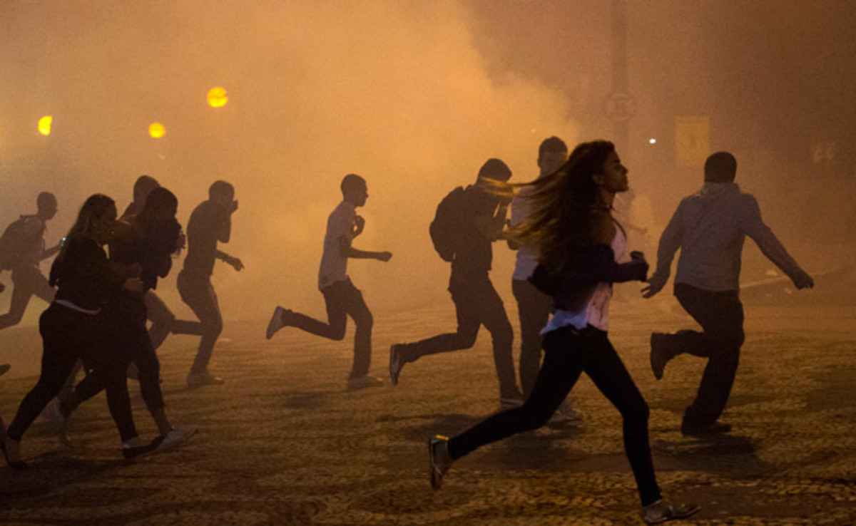 Protesters run from a cloud of tear gas released during a protest in Rio de Janeiro on Thursday.
