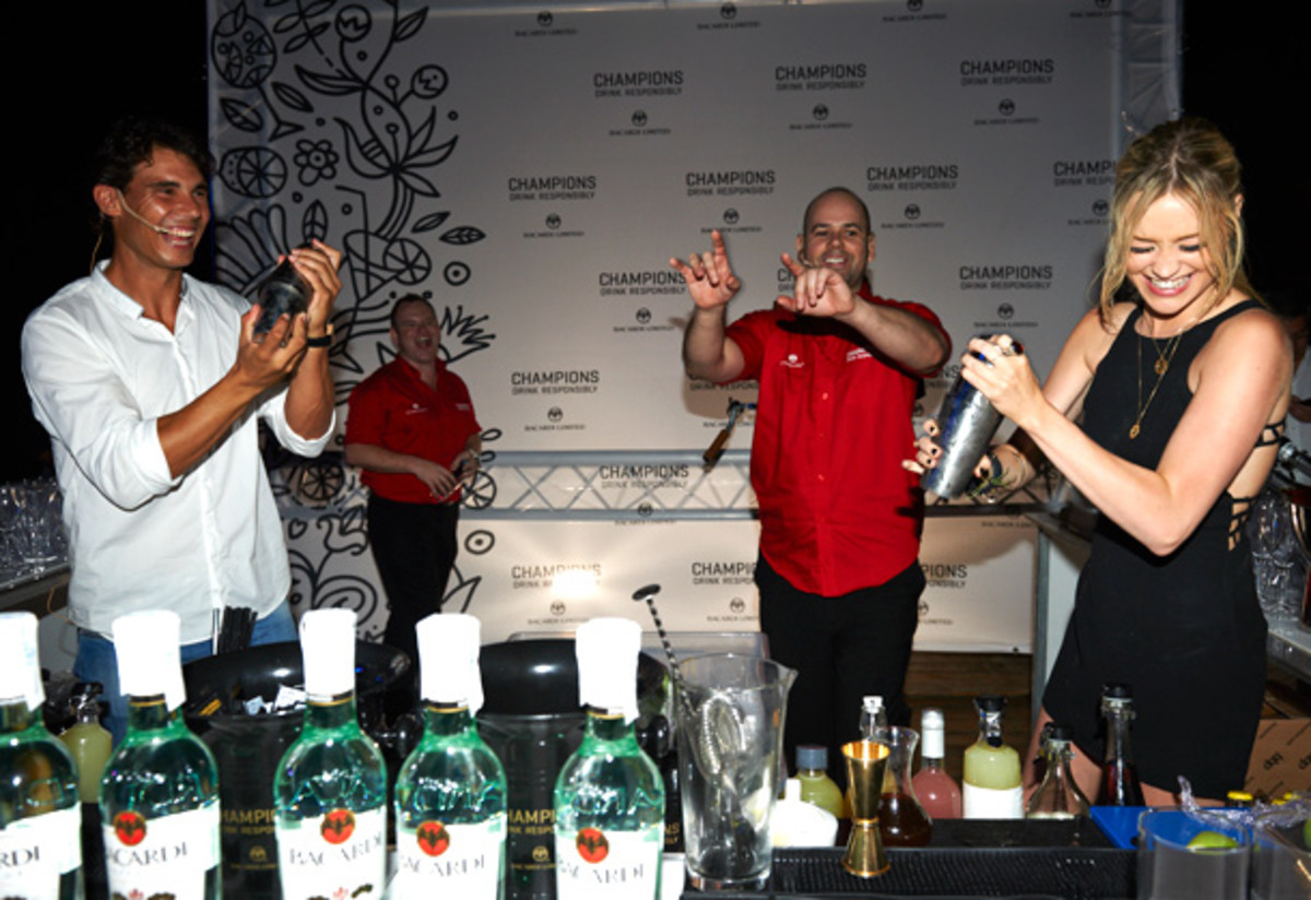 Nadal and TV present Laura Whitmore (right) shake up some drinks for the guests. (Getty Images for Bacardi)