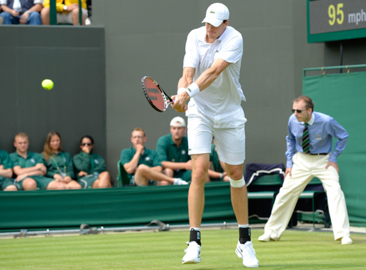 John Isner tried to play through a freak knee injury suffered in the second round at Wimbledon, but he ultimately retired. (ADRIAN DENNIS/Getty Images)
