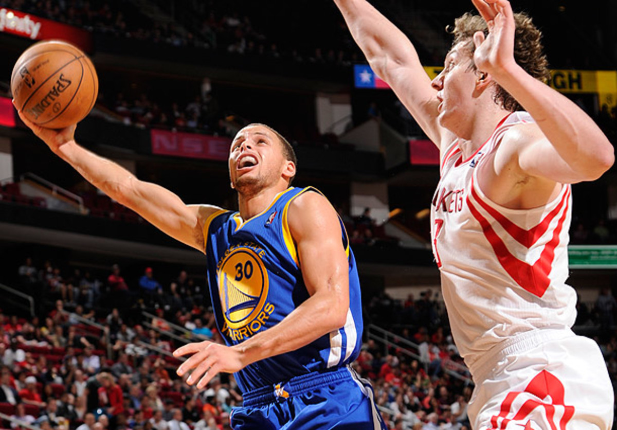 Stephen Curry goes for a layup against Omer Asik