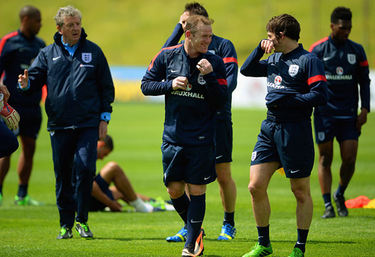 England manager Roy Hodgson (left) looks on as teammates Wayne Rooney (center) and Leighton Baines chat.