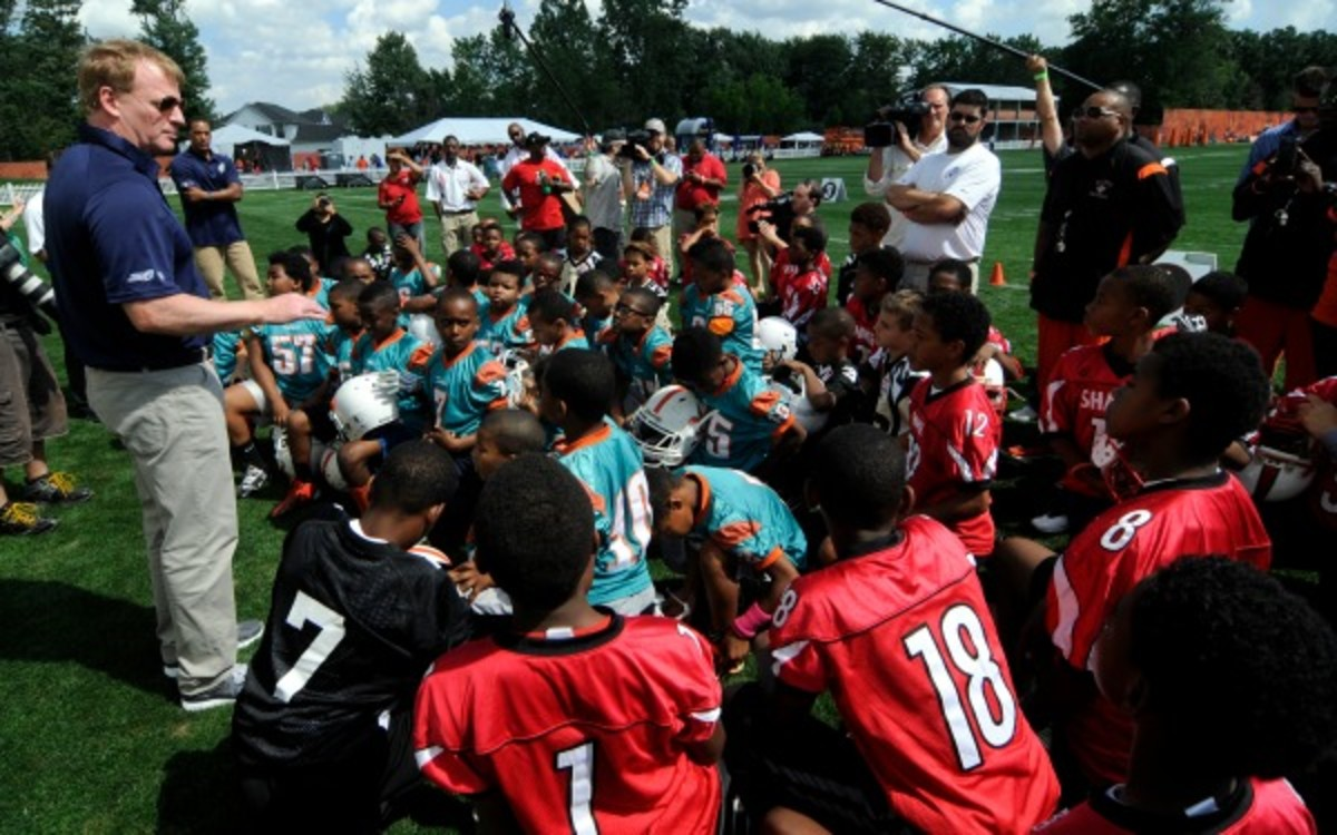 NFL Commissioner Roger Goodell talks with youth football players. (Tom E. Puskar/ AP Images for NFL Network)